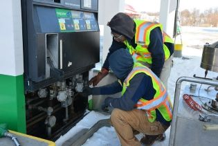 Two individuals inspect a fuel pump from the DATCP Bureau of Weights and Measures.